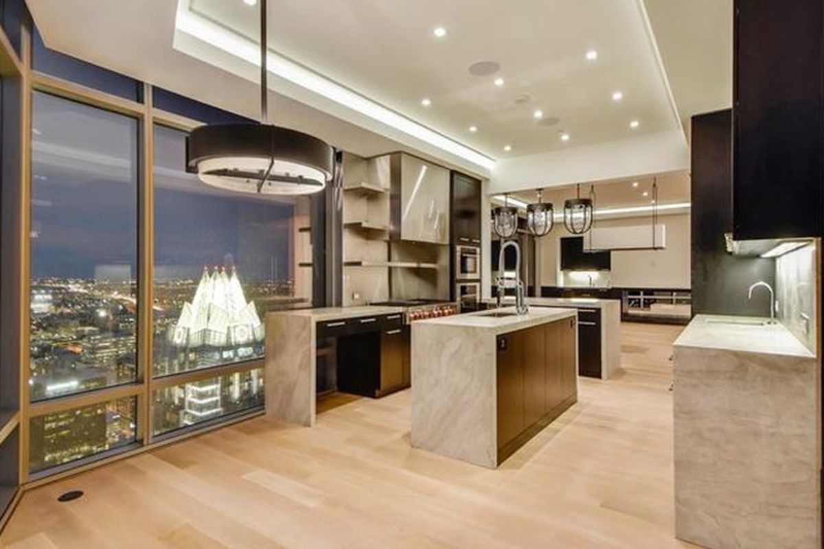 Open, unfurnished condo with light wood floors, open kitchen, downtown views from giant window wall