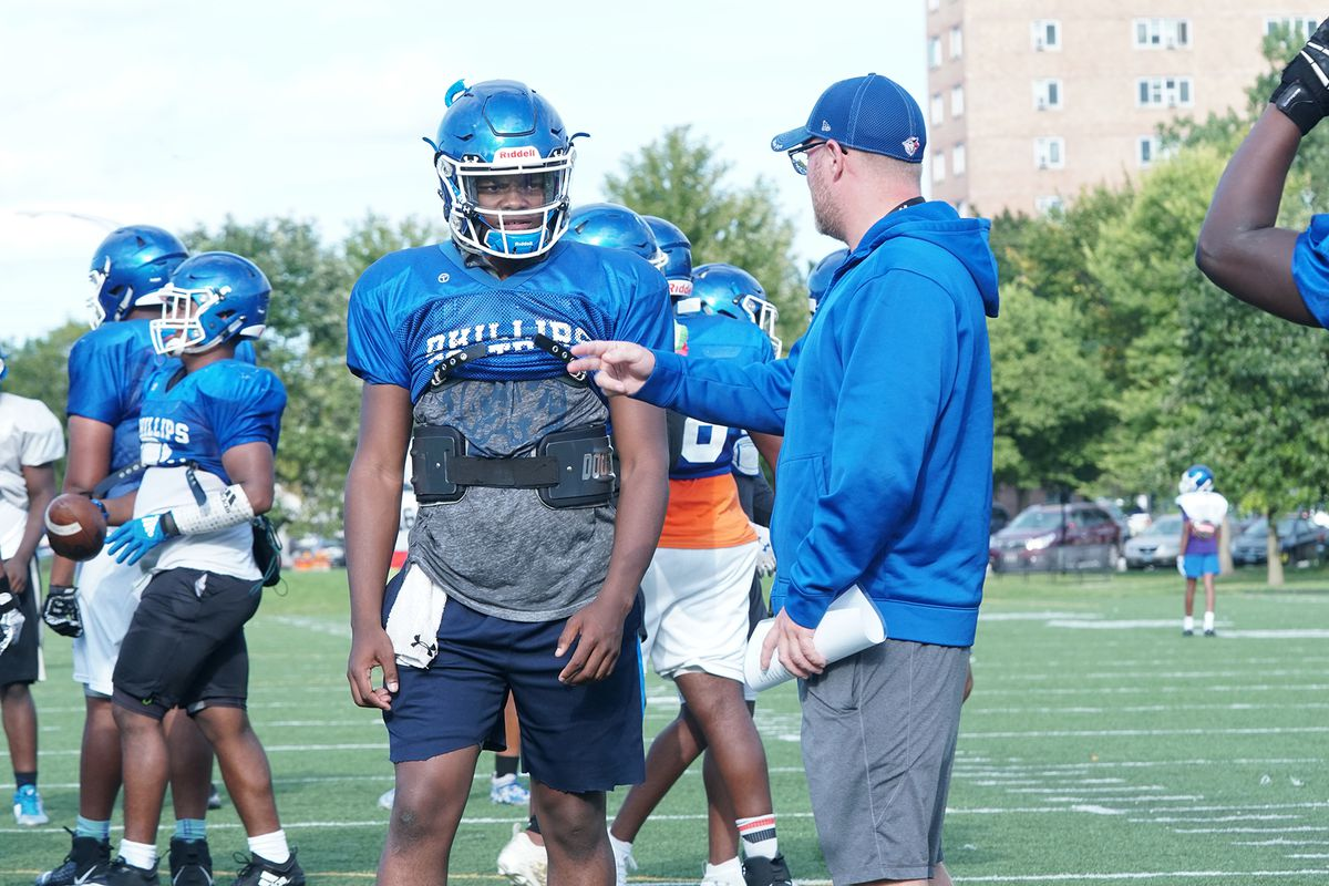 Phillips football coach Troy McAllister talks to Terryon Thrower during a practice last September.