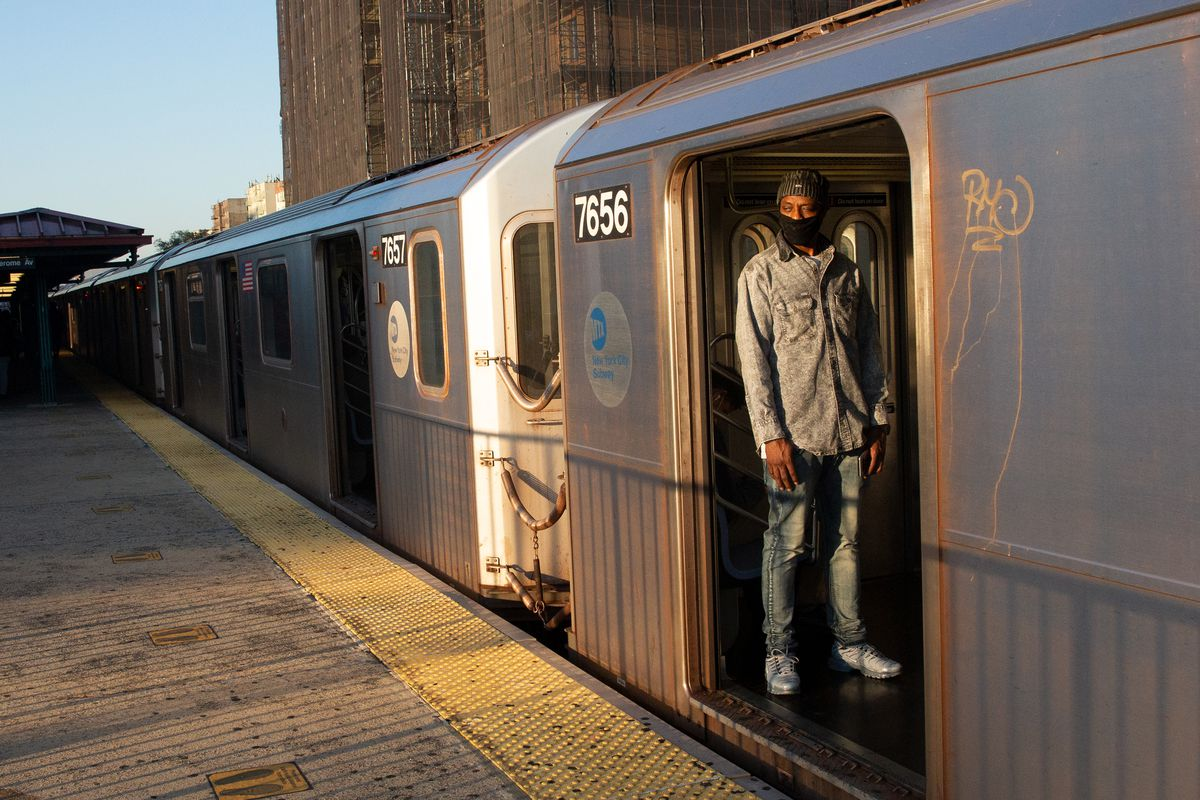 People take a 4 train in the Bronx during the morning commute, Oct. 1, 2020.