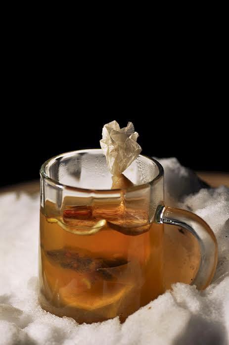 A steamy clear mug is garnished with a lemon
