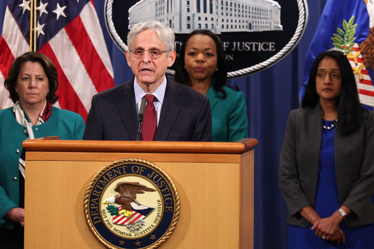 Attorney General Merrick Garland at a lectern with three people standing behind him.