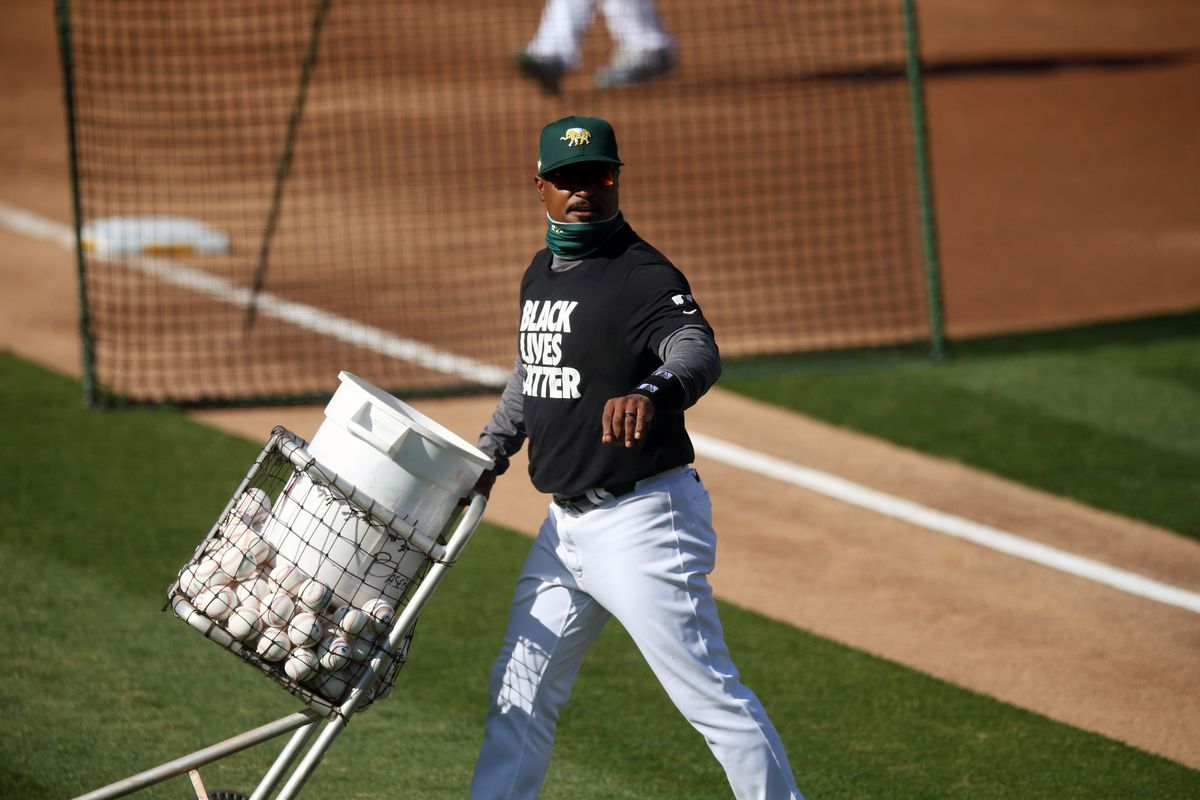 Oakland Athletics assistant hitting coach Eric Martins (62) with bucket of baseballs during batting practice before game vs Los Angeles Angels at RingCentral Coliseum.