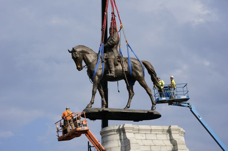 Crews work Wednesday to remove one of the country's largest remaining monuments to the Confederacy, a towering statue of Confederate General Robert E. Lee on Monument Avenue in Richmond, Va.
