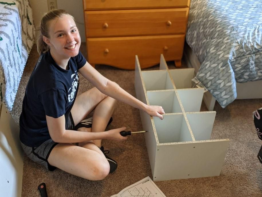 A young woman assembles furniture as part of an on-going service project to furnish apartments for incoming refugee families in Houston.