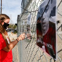 University of Utah women's soccer player Hillary Noakes hangs a picture at the Say Their Names Memorial in Salt Lake City on Saturday, Sept. 26, 2020.