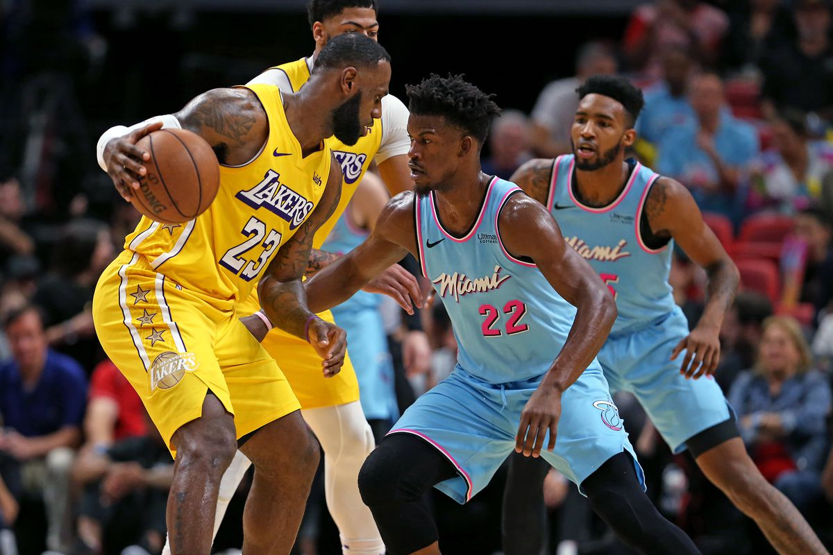 The Los Angeles Lakers' LeBron James works agains the Miami Heat's Jimmy Butler in the first quarter at the AmericanAirlines Arena in Miami on Friday, Dec. 13, 2019.