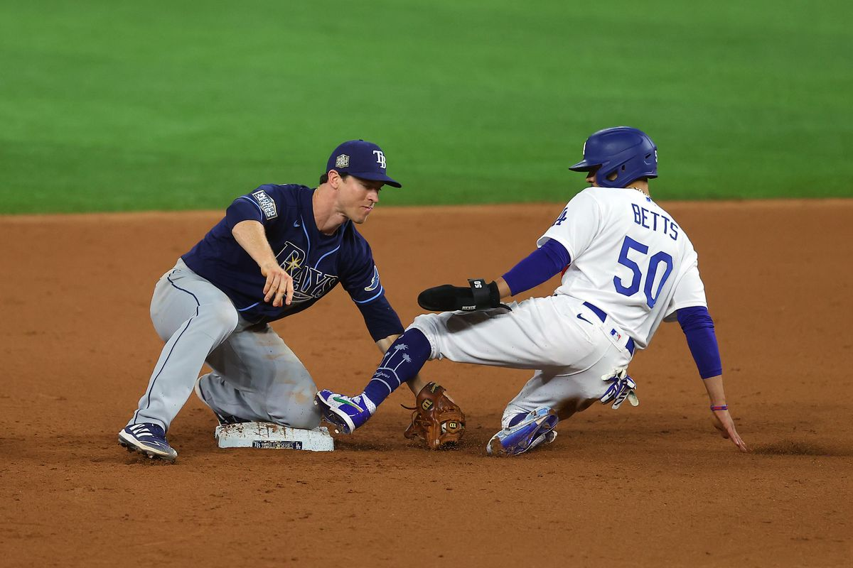 Mookie Betts #50 of the Los Angeles Dodgers is tagged out by Joey Wendle #18 of the Tampa Bay Rays during the eighth inning in Game One of the 2020 MLB World Series at Globe Life Field on October 20, 2020 in Arlington, Texas.