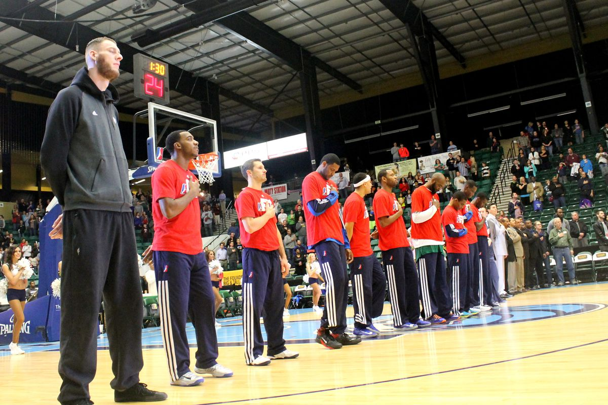 Paul Sturgess stands on the court with his teammates during the national anthem.