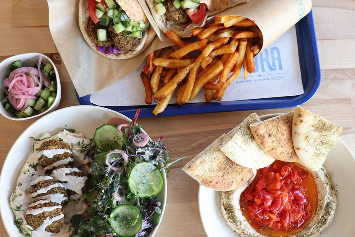 overhead view of a wooden table with a tray of dishes: pita sandwich and fries, bowl of hummus with pita bread triangles, and a green salad with falafel