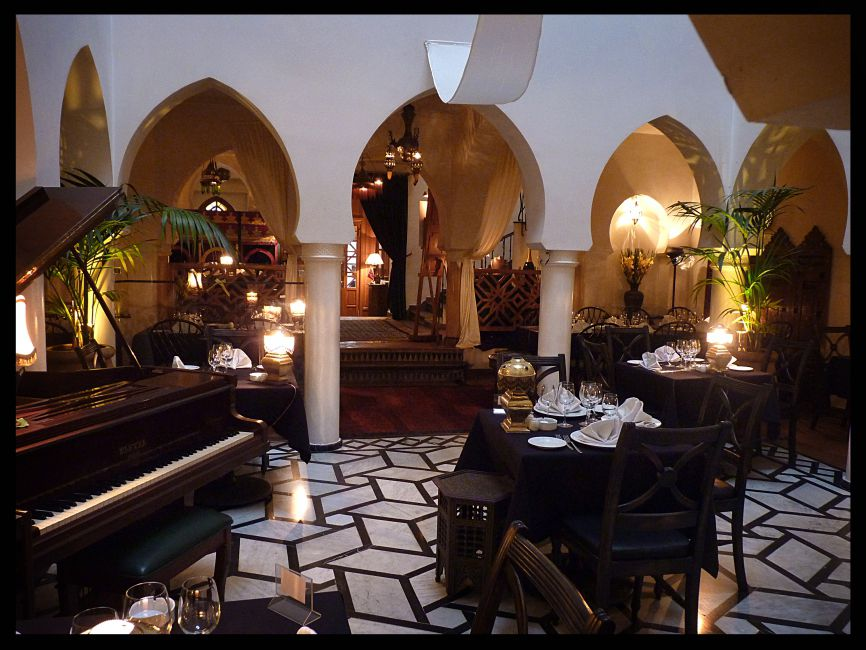 A dining room with mood lighting, a piano, plants and Moroccan designs