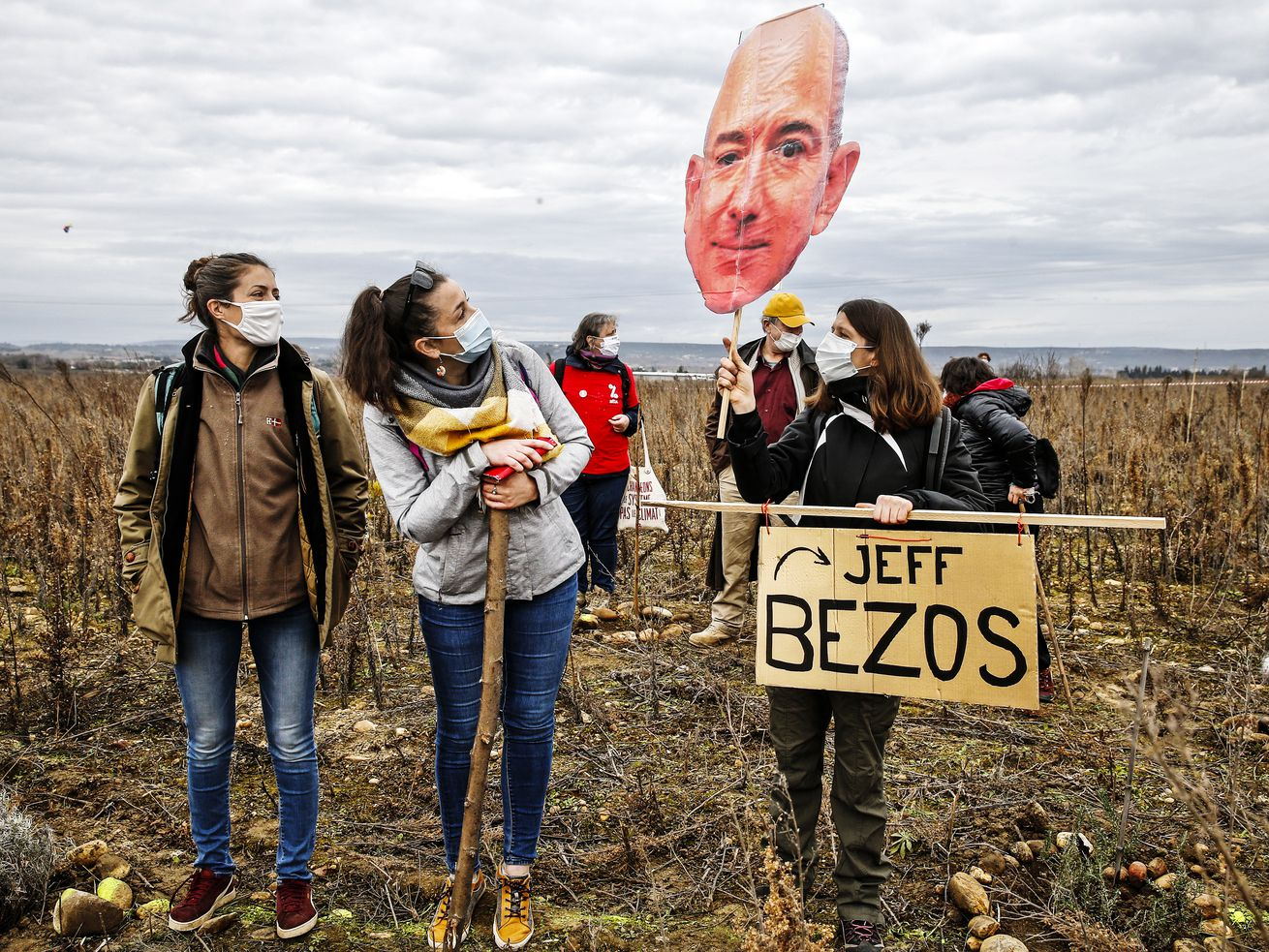"Protesters standing in a scrubby field and holding a cutout of Jeff Bezos's face along with a sign saying ""Jeff Bezos."""