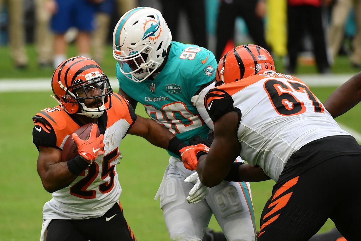 Cincinnati Bengals running back Giovani Bernard (25) runs the ball into Miami Dolphins outside linebacker Shaq Lawson (90) during the second half at Hard Rock Stadium.