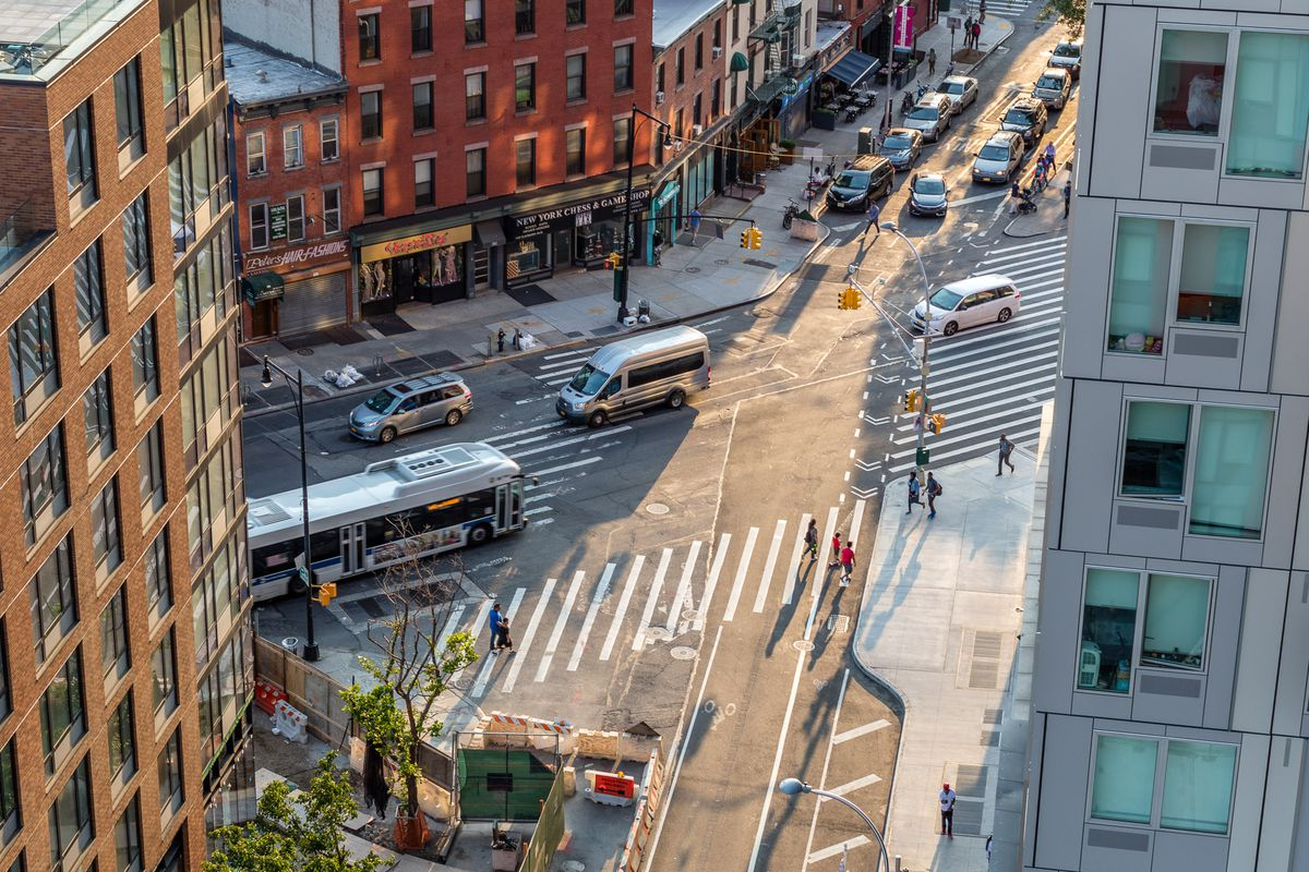 A view onto a street with cars and buses and pedestrians in the crosswalk.