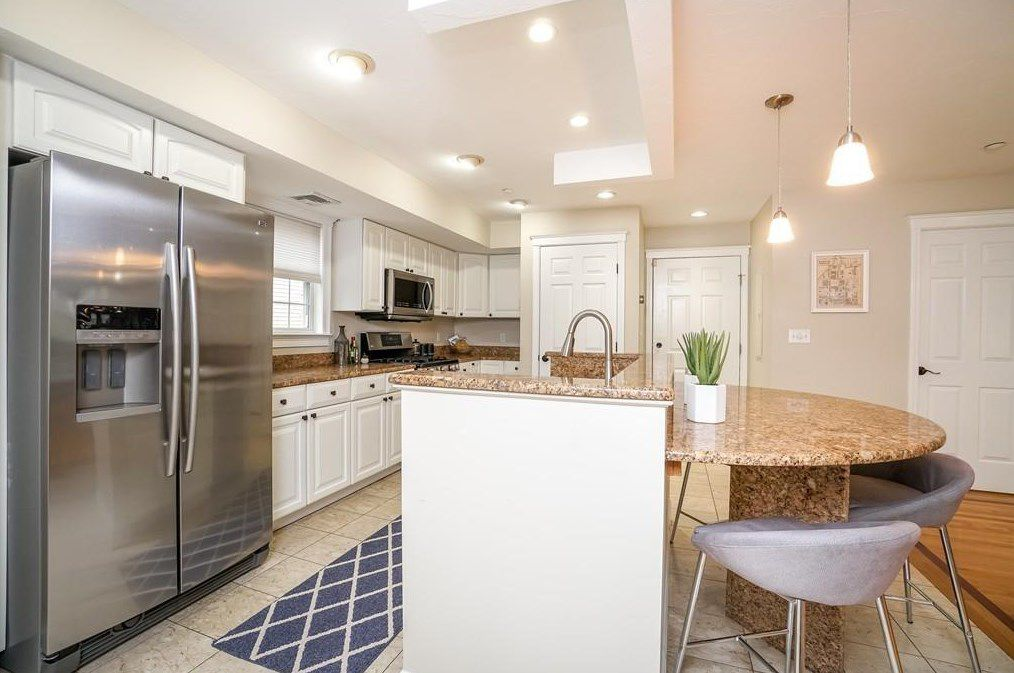 An open kitchen with an island that's rounded on one side and a run of counters opposite it.