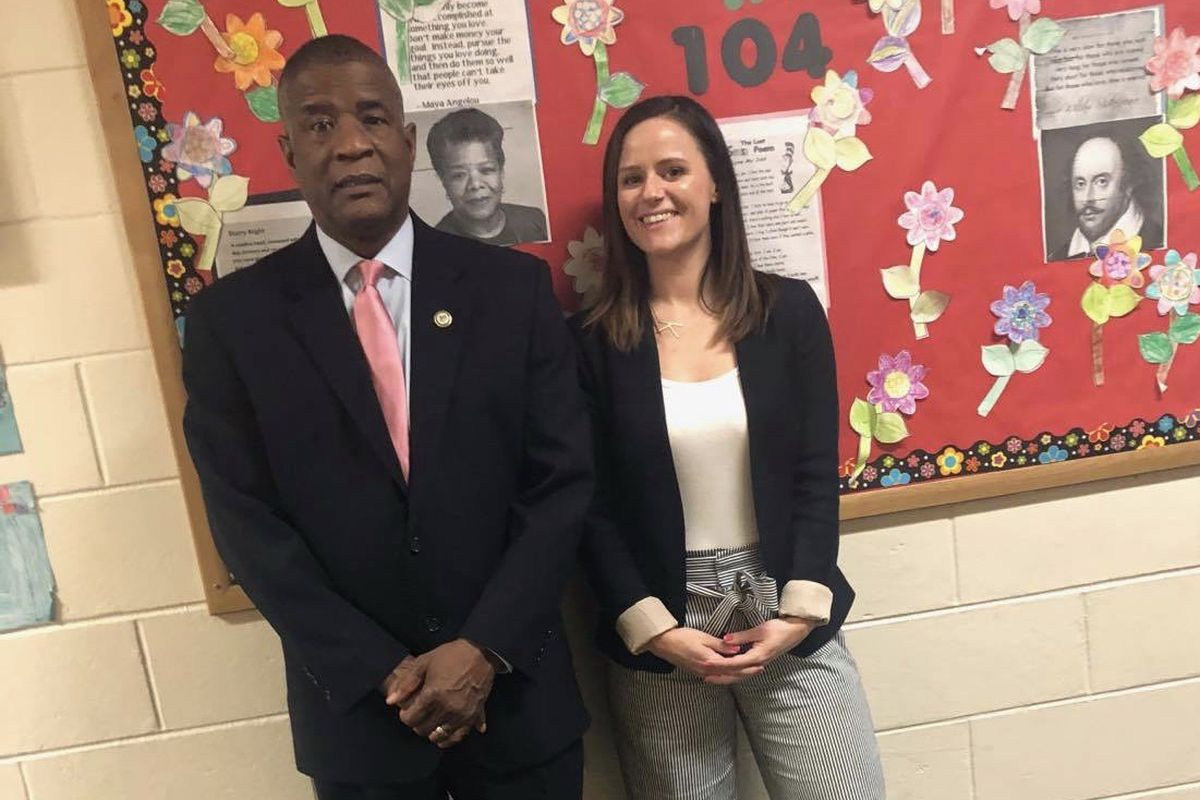 A man and a woman stand in front of a school bulletin board.