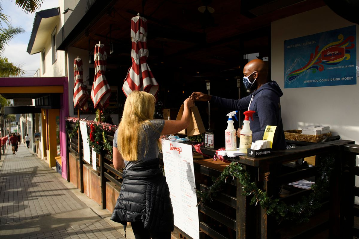 A patron receives take-out food from a restaurant due to Covid-19 restrictions on restaurant outdoor dining in Manhattan Beach, California.
