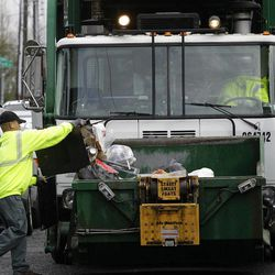Anousone Sudettanh, an employee of Waste Management Inc., collects garbage for the city of Seattle, Thursday, April 5, 2012. City officials are now weighing switching to every-other-week garbage collection from the currently weekly pick-up rate, and the city council is considering whether to test the concept in about 800 single-family homes in four areas this summer.