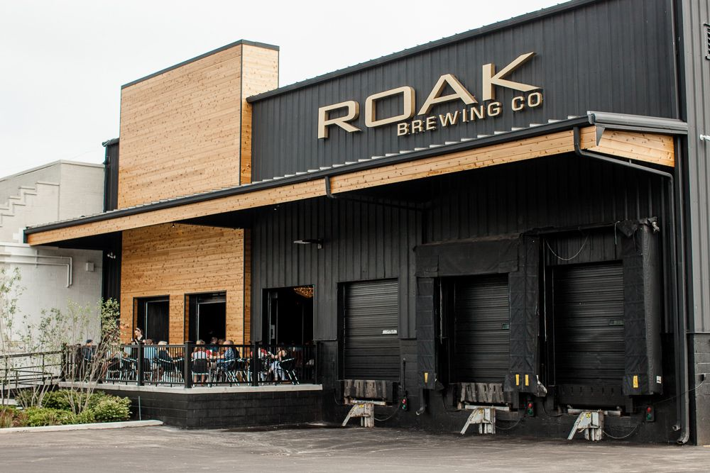 The exterior of Roak on a cloudy day. The building looks like a warehouse with black corrugated metal and wood planking around the entrance.