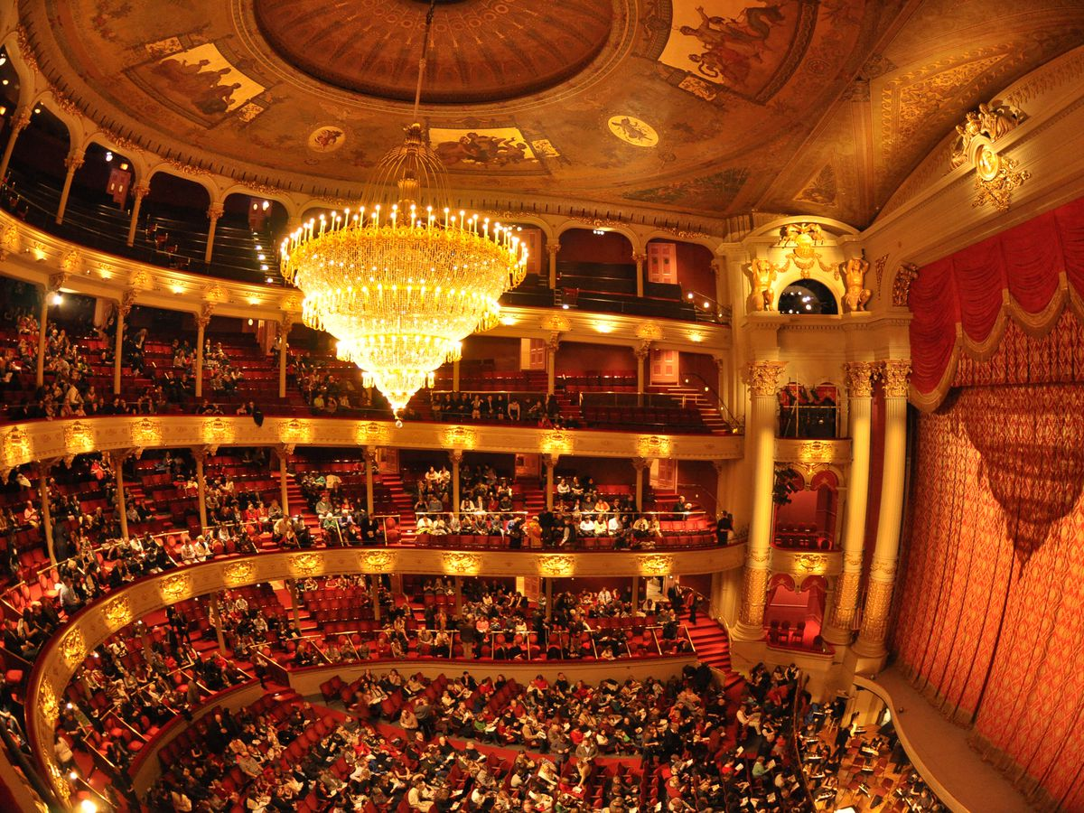 The interior of the Academy of Music in Philadelphia. There multiple balconies and many rows of seats. The stage has a curtain over it.
