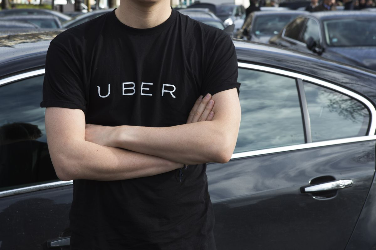 Uber driver in an Uber shirt in front of a black car