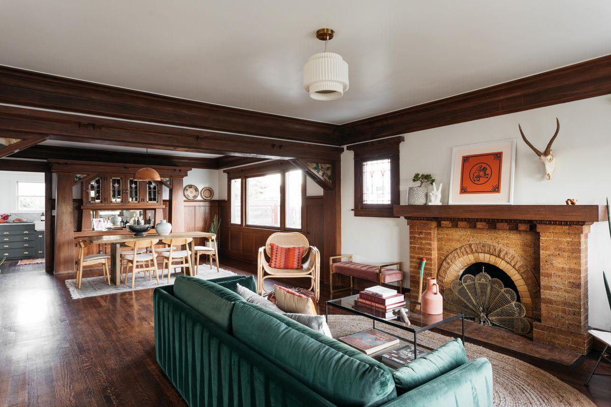 Living room with a green sofa, brick fireplace, and dining area toward the back.