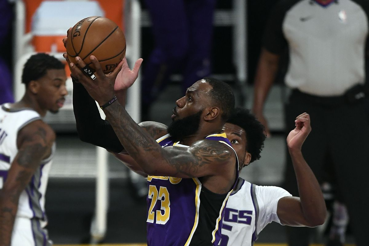 LeBron James #23 of the Los Angeles Lakers scores a basket against Damian Jones #15 of the Sacramento Kings and gets fouled during the first half at Staples Center on April 30, 2021 in Los Angeles, California.