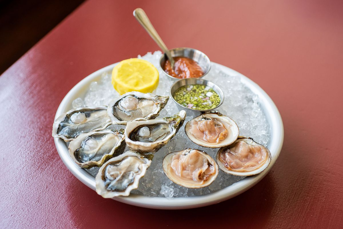 Oysters and clams on ice at Found Oyster with a red table.