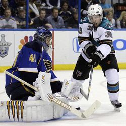San Jose Sharks' Logan Couture, right, tries to reach a loose puck as St. Louis Blues goalie Jaroslav Halak, of Slovakia,   defends during the first period in Game 2 of an NHL Stanley Cup first-round hockey playoff series Saturday, April 14, 2012, in St. Louis.