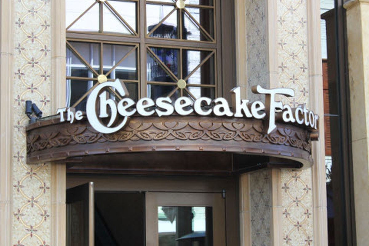 Signage of Cheesecake Factory in white letters over a brass overhang at The Grove in Los Angeles.