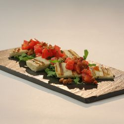 Grilled goat cheese on arugula salad, with salsa made of duck cracklings and tomato
