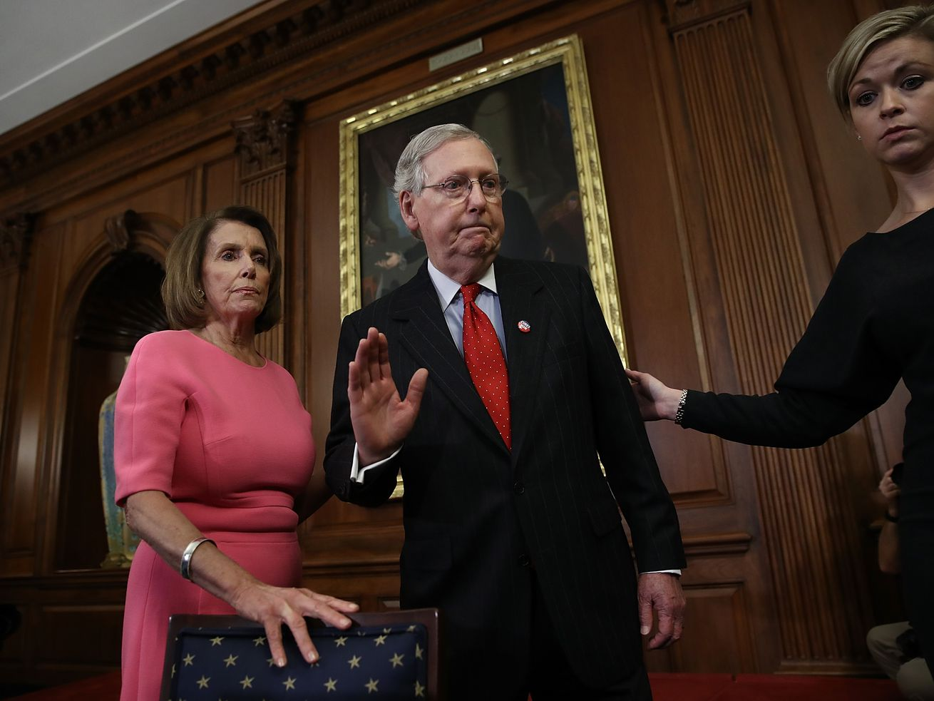 Senate Majority Leader Mitch McConnell waves goodbye after speaking with House Speaker Nancy Pelosi at an event in 2016. The two leaders now must reach a deal on humanitarian aid to the border.
