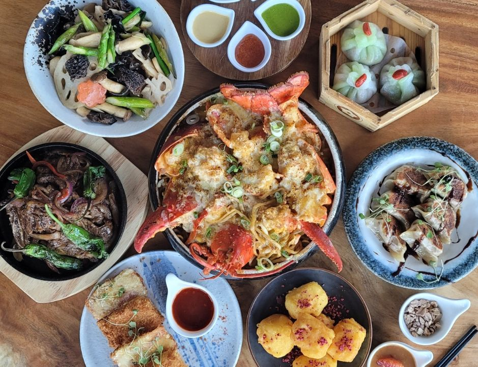 Spread of Lunar New Year dishes plated on a table, including potstickers and lobster noodles