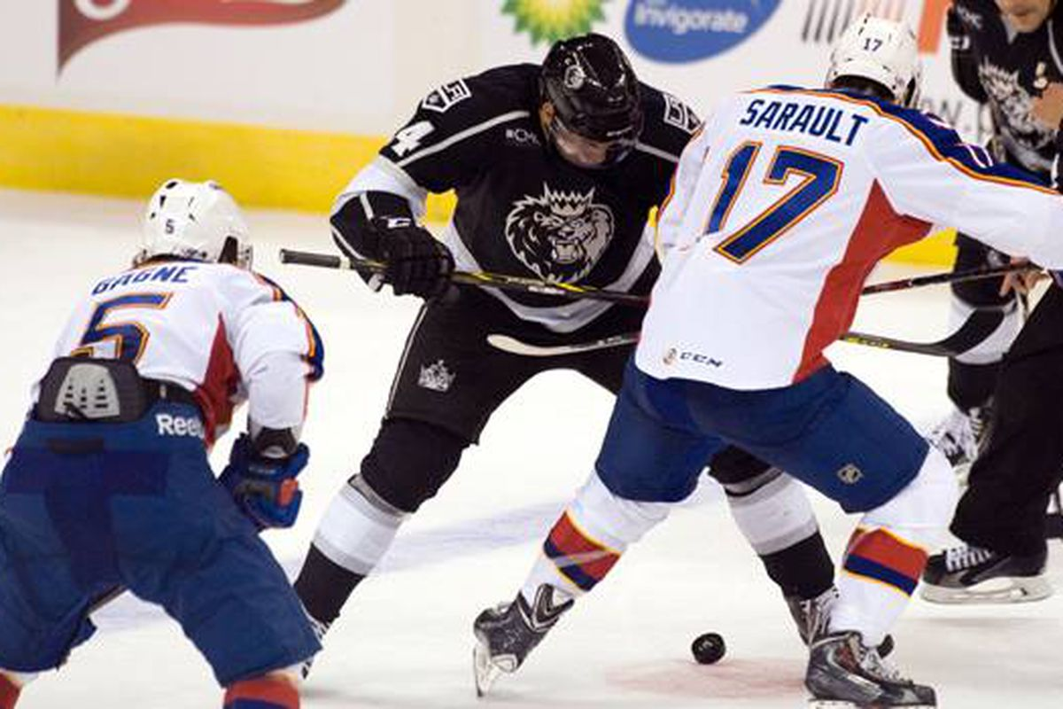 Charlie Sarault fights for the puck in the face off circle while flanked by defensemen-turned-winger Kevin Gagne Oct 18.2014 versus Manchester Monarchs