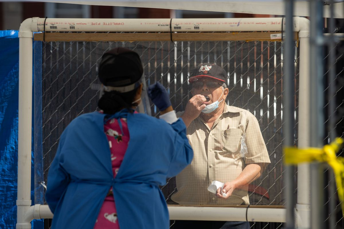 A person conducts his own COVID-19 mouth swab test at Community Organized Relief Effort's (CORE) COVID-19 testing facility at in Little Village Sept. 4.