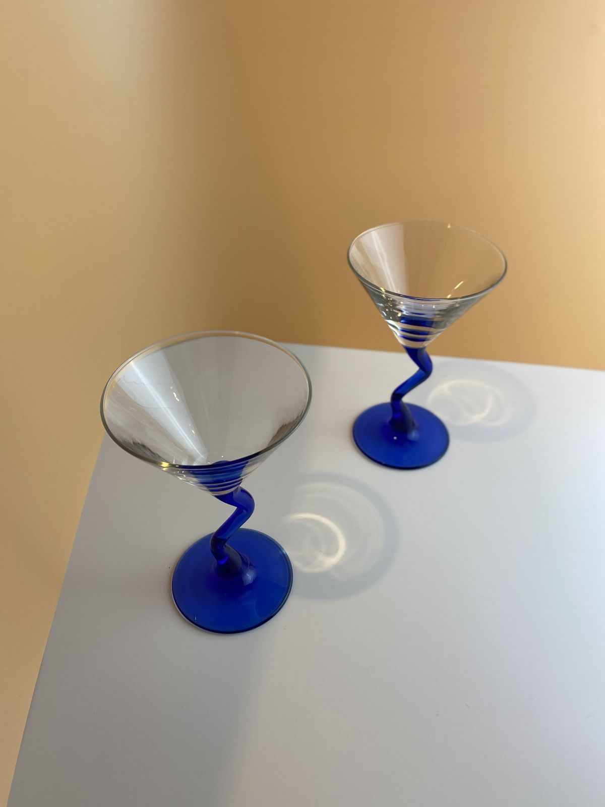Two martini glasses with wavy, blue stems