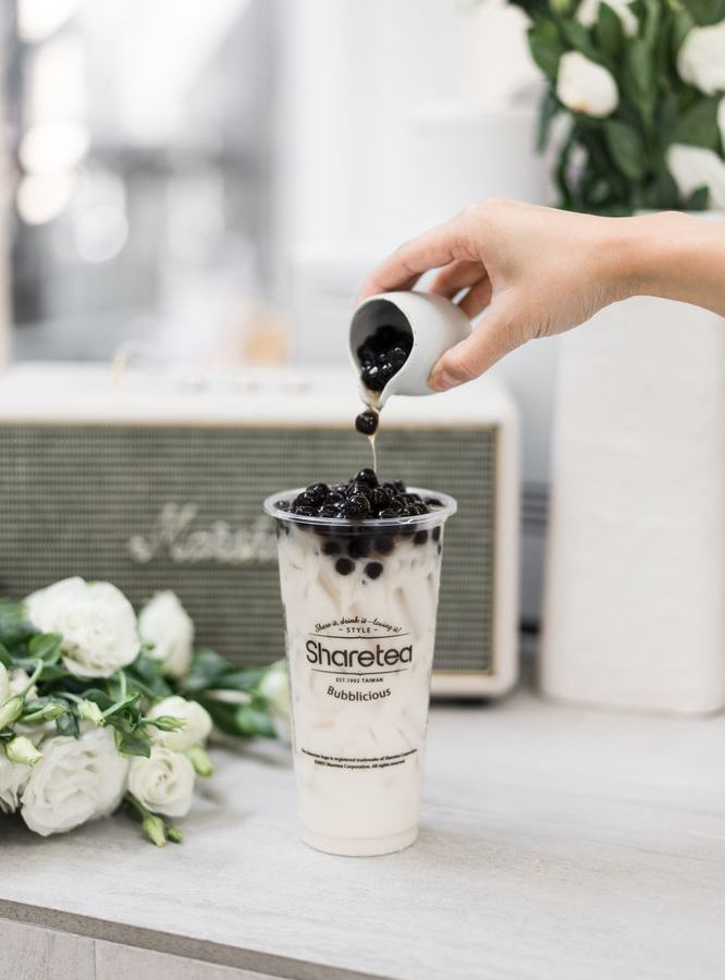 A hand pours black boba into a plastic Sharetea cup filled with white milk tea.