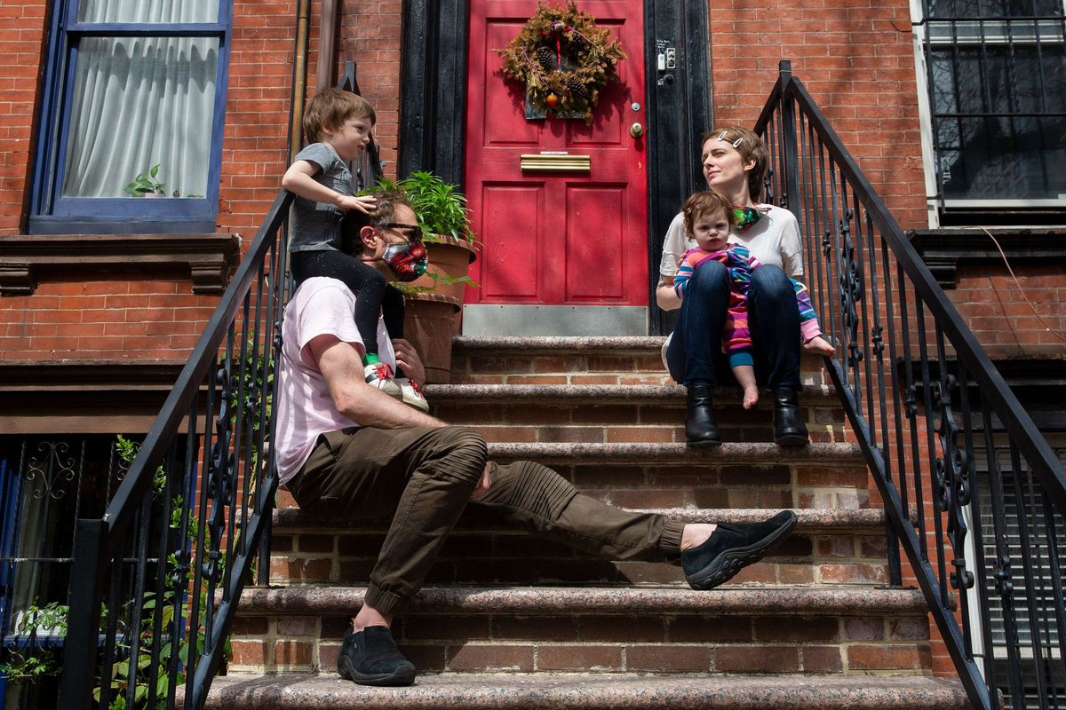 Karl Jacob and Catherine LaSota enjoy some time in the sun with their children, Gaius and Adina, outside their Long Island City home.