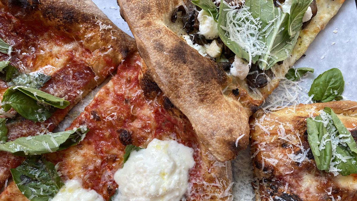 A truffle slice, spicy salami slice, burrata slice, and square slice at L'Industrie sit on a paper, with green basil and white parmesan dotting every slice