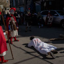 Isaac Bucio, who plays Jesus Christ, falls to the ground during the Via Crucis procession in Pilsen, Friday morning, April 2, 2021. The annual Via Crucis is a Good Friday tradition that reenacts the Stations of the Cross, a Catholic devotion that recounts Jesus' passion and death.