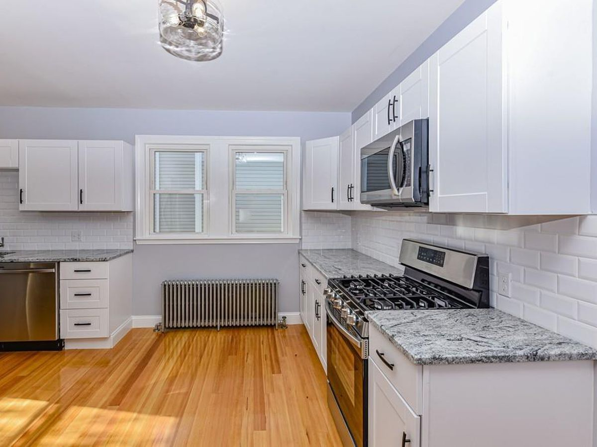 An open kitchen with a long counter that leads toward a radiator below a window.