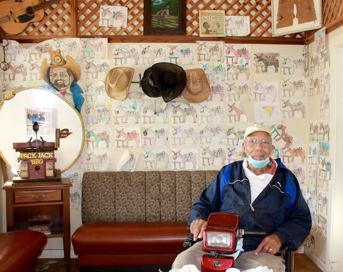 Founder Donnie Harris Sr. inside Pack Jack Barbecue. The walls are lined with cowboy hats and coloring sheets of his pet mule, Pack Jack.