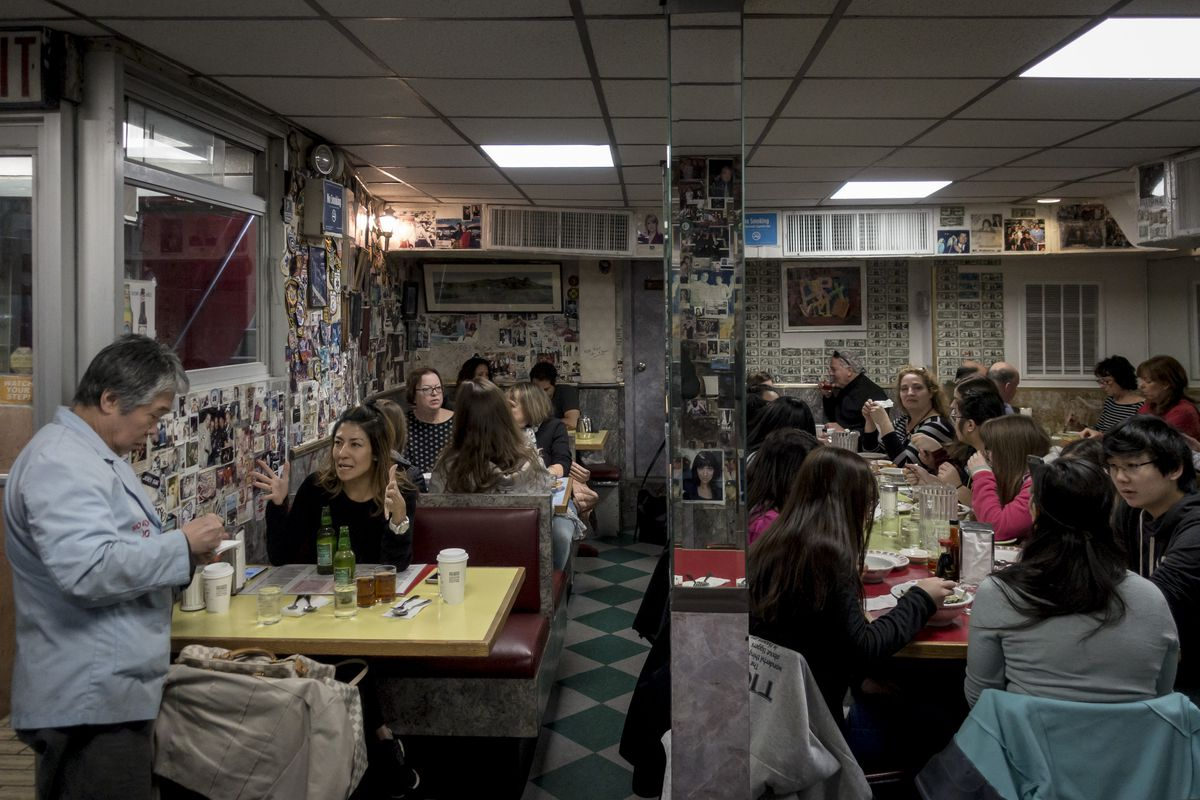 A waiter takes a customers order in a busy diner whose walls are lined with photos and dollar bills