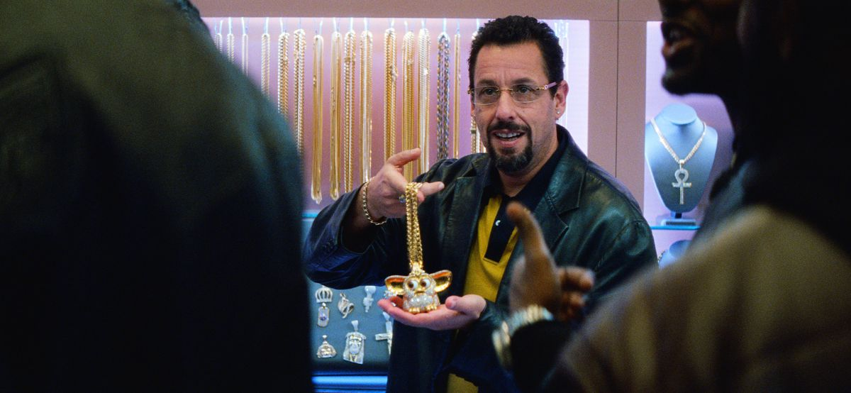 adam sandler's uncut gems character howard holds a jewel encrusted furby on a gold chain
