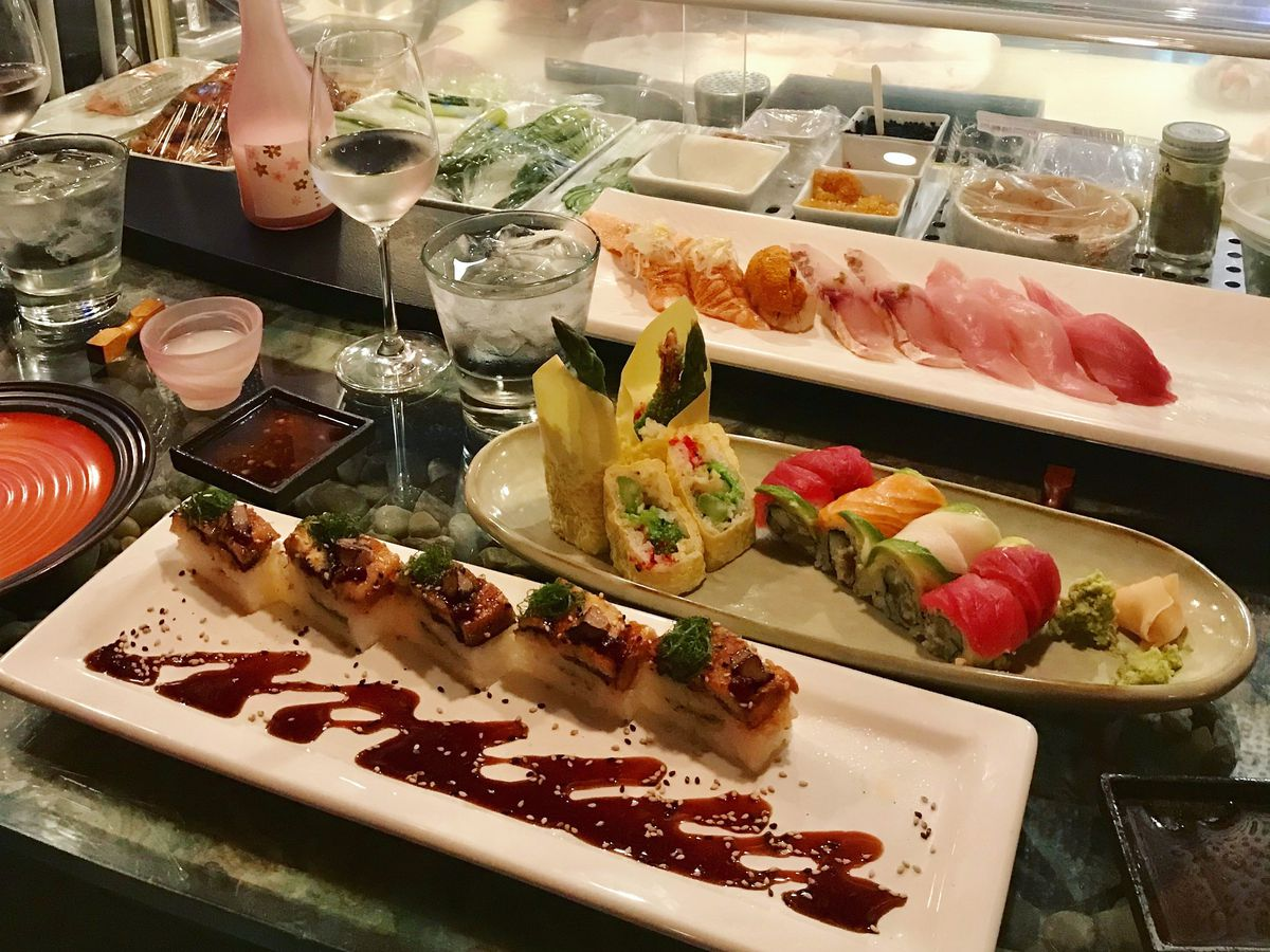 Plates of intricate maki rolls and nigiri, along with sake and wine, in front of a sushi counter where a chef works