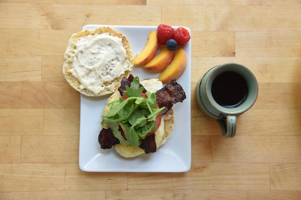 Overhead view of white rectangular plate sitting on a wooden table with a coffee cup on the right side. On the plate sits an open-face English muffin with criss-crossed bacon, tomato, and greens, alongside slices of peach, two raspberries, and a blueberry