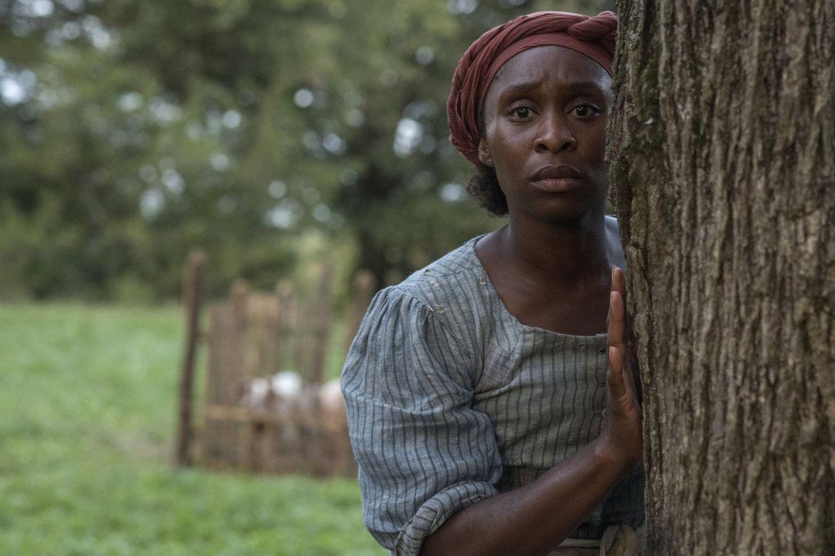 Tubman (Erivo) hides behind a tree.
