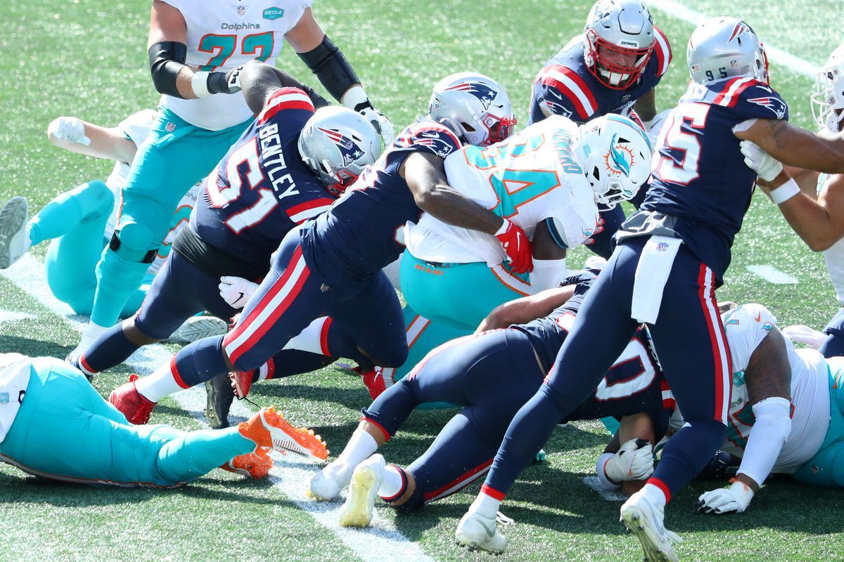 Anfernee Jennings #58 of the New England Patriots tackles Jordan Howard #34 of the Miami Dolphins during the second half at Gillette Stadium on September 13, 2020 in Foxborough, Massachusetts.