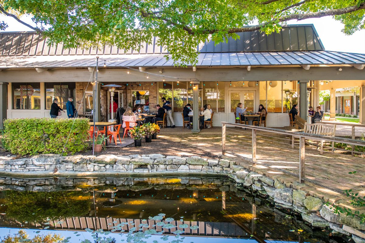 A pond lined by a stone fence in front of a restaurant patio with diners in front of a one-story building with trees