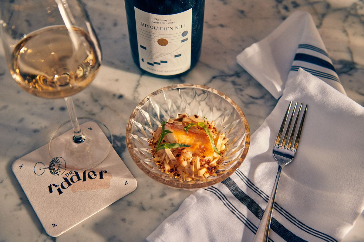 A shallow clear bowl of king crab with almonds sits next to a glass of Champagne