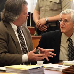 Defense attorney Travis Currie, left, talks to Steven Powell, on the second day of his trial for voyeurism charges in the Pierce County Superior Court house, in Tacoma, Washington, Tuesday, May 8, 2012.